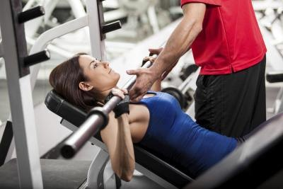 A woman does bench presses with the help of a trainer.