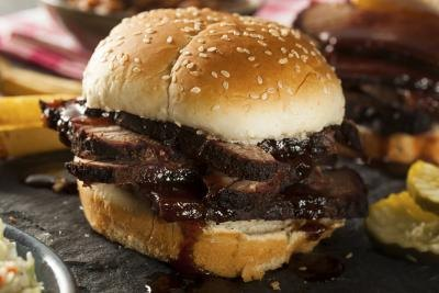 A brisket sandwich with baked beans.