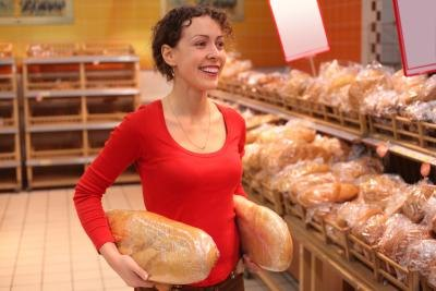 A customer carries two loaves of bread.