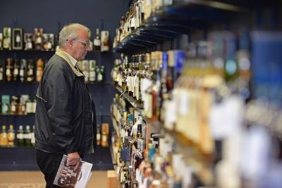 Man admires bottles of whiskey at auction