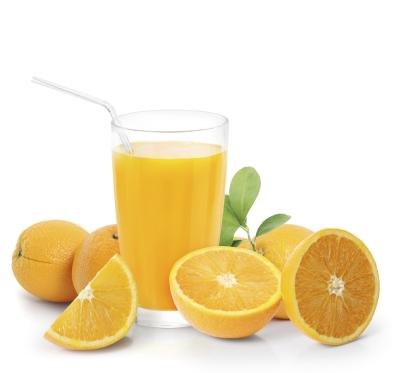 Cup of orange juice surrounded by fresh oranges.