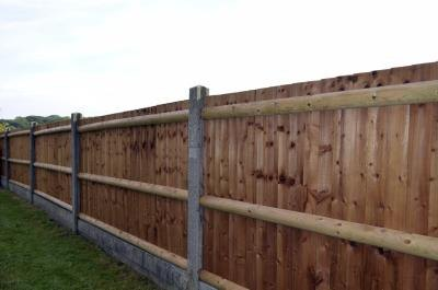 Fence with wooden slats and concrete posts