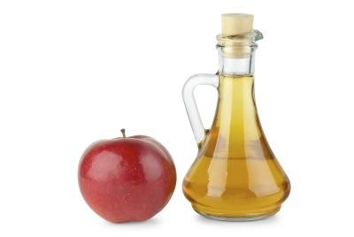 Decanter with vinegar and an apple on the side.