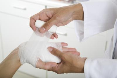 A doctor applies a bandage to a patient's palm.