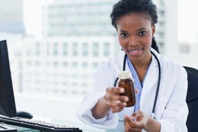 internal medicine doctor holding out prescription bottle