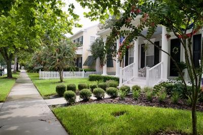 A sidewalk in a neighborhood with attractive homes.