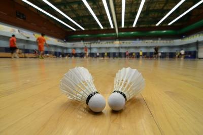 Two shuttles sit on an indoor badminton court.