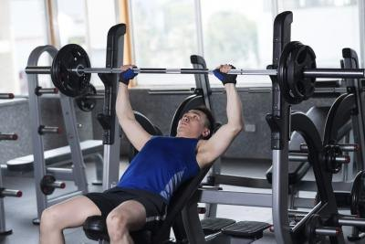 Man bench pressing weights in a gym