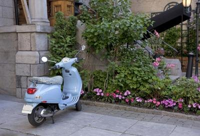 A powder blue scooter is parked outside of a residence.