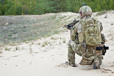 A U.S. soldier kneels in the sand during a desert operation.
