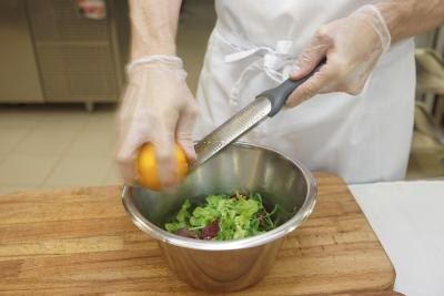 A chef wears gloves and an apron while zesting a lemon.