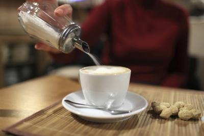 A woman pouring white sugar into a cup of coffee.