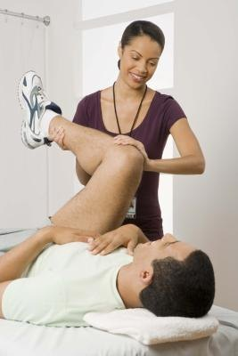 An assistant or physical therapist helps with a hip flexor stretch.