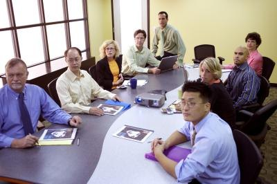 Employees sit at a curved table that divides into two in a conference room.