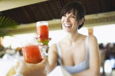 Woman toasting with strawberry daiquiri