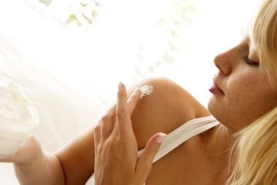 woman applying lotion to shoulder