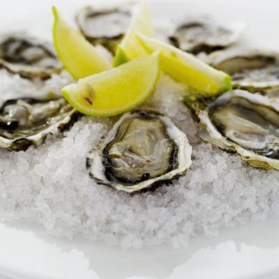 Oysters in the half shell served with lemon slices on a bed of sea salt.