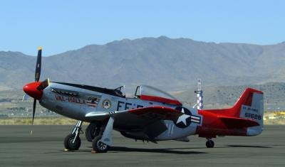 A vintage single-engine military aircraft sits on a runway.