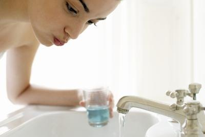 Young woman using mouth wash