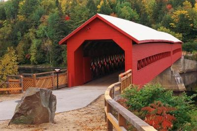 A wooden covered bridge spans a river.