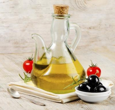 A bottle of olive oil with a some black olives and tomatoes