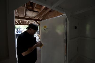 Man puts final touches to storm safe room door in Neosho, Missouri