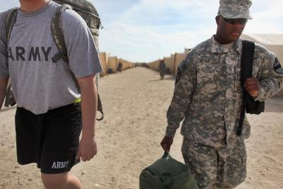 Army sergeant carry gear to staging area