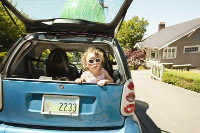 Young girl in the back of a Smart Car.