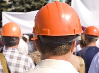 Members of a labor union wearing orange helmets.