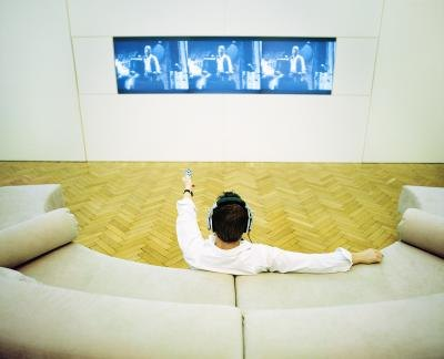 Man relaxing at home watching a plasma screen