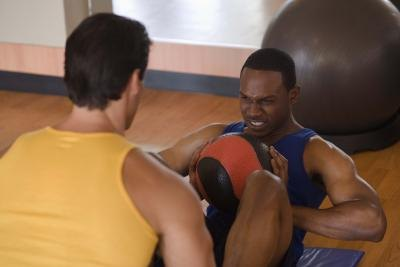 Two men exercise with a medicine ball in a work out studio.