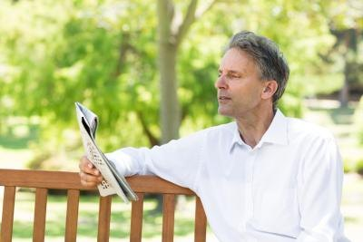 Man reading a newspaper on a park bench