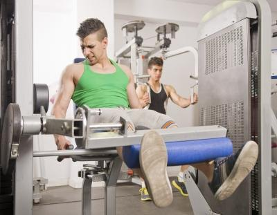 Young man doing quad exercises in gym