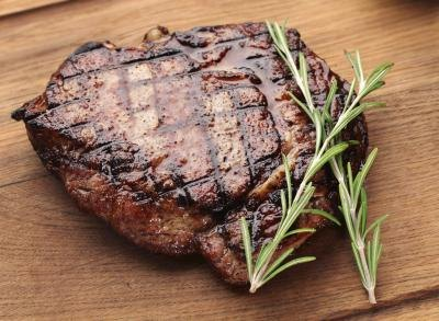 A grilled steak on a cutting board.