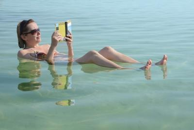 Woman reads a book while floating in the Dead Sea