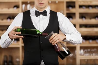Waiter in tuxedo pouring wine