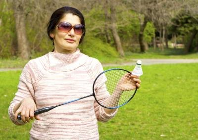 A woman holds a badminton racket and shuttle outside.