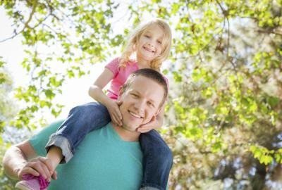 A little girl rides on her daddy's shoulders outside in the trees.