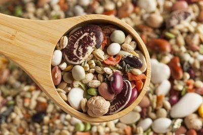 Large wooden spoon filled with an assortment of beans