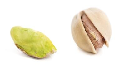Two pistachios one shelled, and one without the shell.