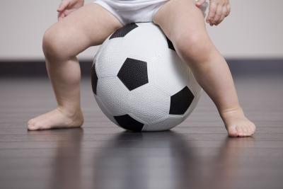Baby sitting on a soccer ball.