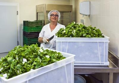 A hospital food worker prepares tossed green salads.