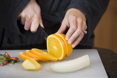 A woman slices an orange and banana.