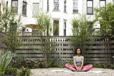 A young woman sits in bound angle pose on an urban patio.