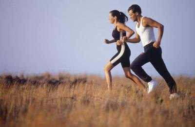 A couple jogs through a field.