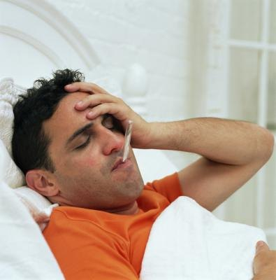 Adult male sick in bed with the flu