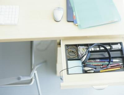 An open drawer attached to a desk.