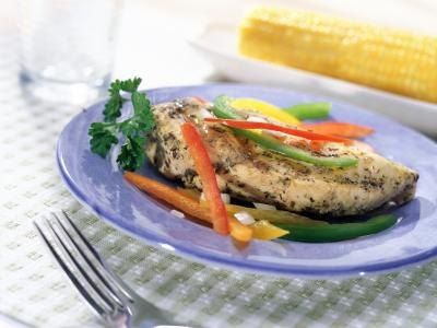 A plate of grilled chicken and vegetables.