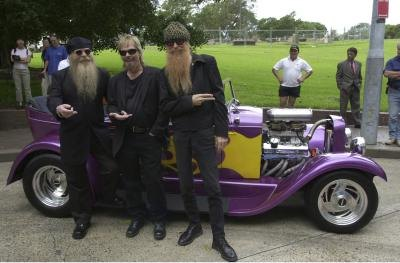 Rock band ZZ Top pose in front of hot rod