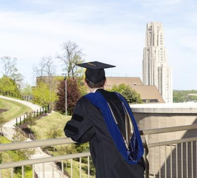 Doctorial graduate looking over the Cathedral of Learning at the University of Pittsburgh